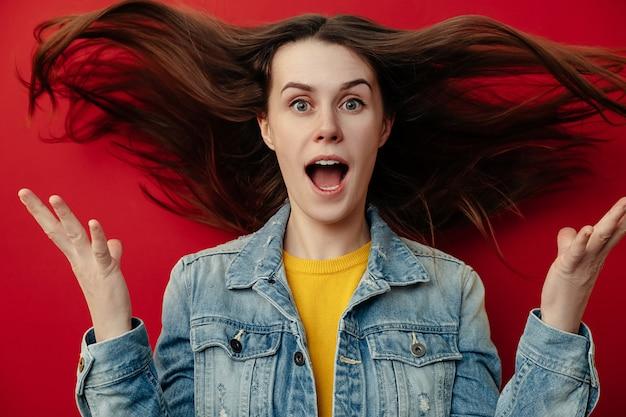Portrait de jeune femme aux cheveux volants en panique regarde avec une expression surprise, se sent nerveux dans une situation stressante, porte une veste en jean, ouvre la bouche avec stupéfaction, isolé sur fond rouge
