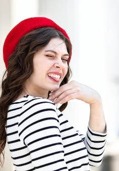 Portrait d'une jeune femme aux longs cheveux noirs dans un béret rouge sur le fond de la ville.
