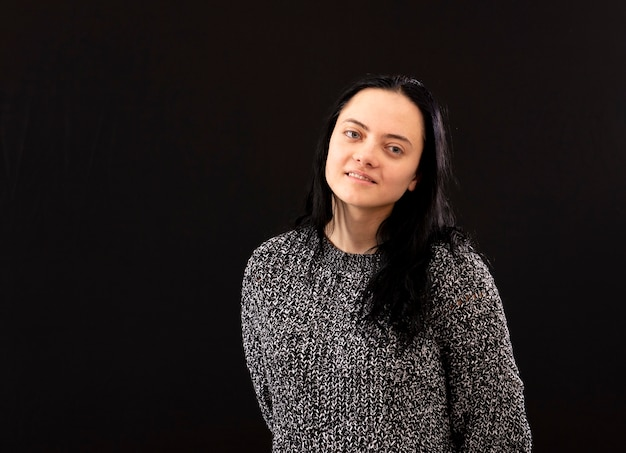 Portrait de jeune femme aux longs cheveux noirs portant un pull en tricot gris