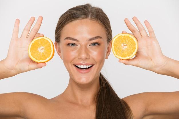 Portrait d'une jeune femme aux seins nus joyeuse isolée, montrant des tranches d'orange