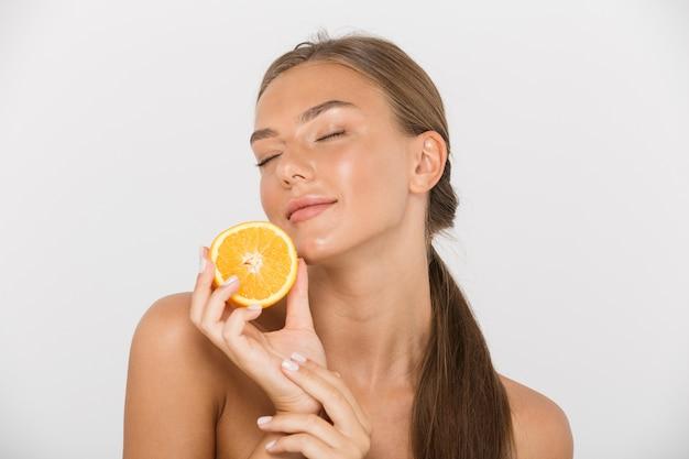 Portrait d'une jeune femme aux seins nus sensuelle isolée, montrant des tranches d'orange