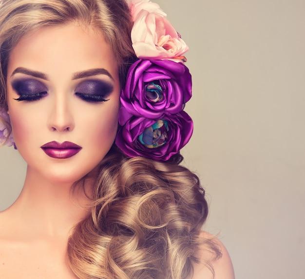 Portrait de jeune femme aux yeux fermés et aux paupières colorées en violet foncé.