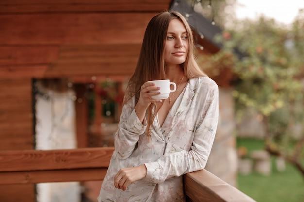 Portrait de jeune femme sur le balcon tenant une tasse de café ou de thé le matin. elle dans une chambre d'hôtel en regardant la nature en été. la jeune fille est vêtue de vêtements de nuit élégants. temps de repos