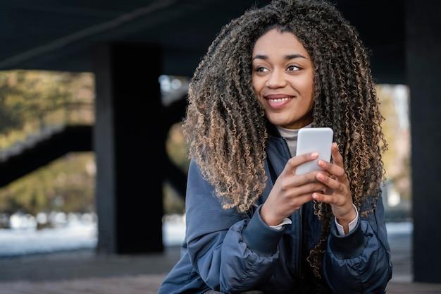 Portrait jeune femme belle à l'aide de mobile