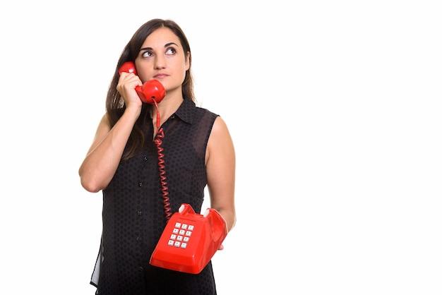 Portrait de jeune femme belle à l'aide de vieux téléphone