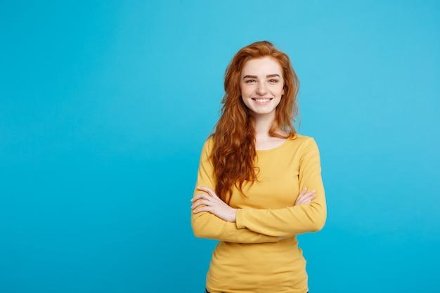 Portrait de jeune femme belle au gingembre avec des taches de rousseur souriant joyeusement isolé sur l'espace de copie de mur bleu pastel