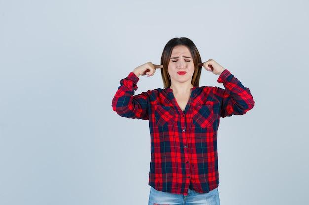 Portrait de jeune femme belle boucher les oreilles avec les doigts en chemise décontractée et à la vue de face ennuyée