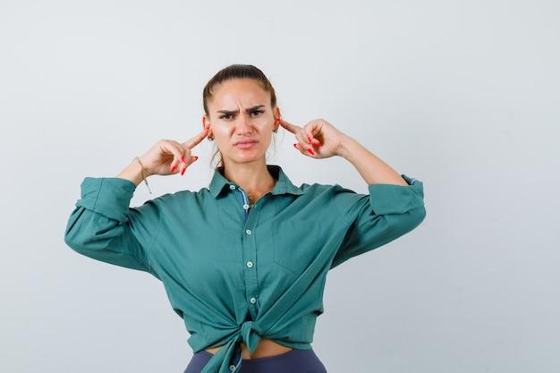 Portrait de jeune femme belle boucher les oreilles avec les doigts en chemise verte et à la vue de face ennuyée
