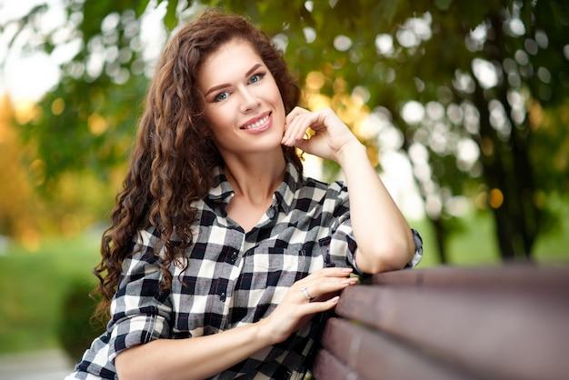 Portrait de jeune femme belle dans une chemise à carreaux et cheveux bouclés en été dans le parc