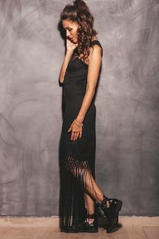 Portrait de jeune femme belle hipster en robe noire d'été à la mode. sexy femme insouciante posant près du mur. modèle brune avec maquillage et coiffure
