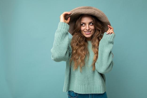Portrait de jeune femme belle hipster en tenue à la mode et chapeau. personne de sexe féminin insouciant sexy posant isolé près du mur bleu en studio avec espace libre. modèle positif avec un maquillage naturel.