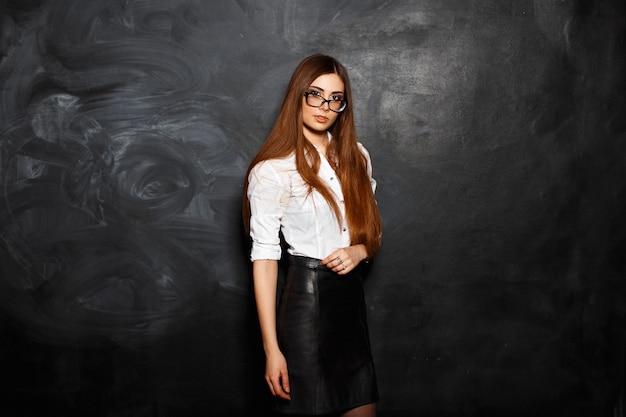 Portrait de jeune femme belle avec des lunettes debout contre un mur noir