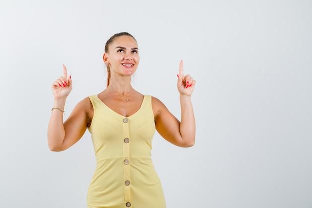 Portrait de jeune femme belle pointant vers le haut en robe et à la vue de face heureuse