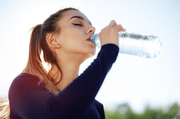 Portrait de jeune femme belle portant de l'eau potable de vêtements de sport bleu au parc