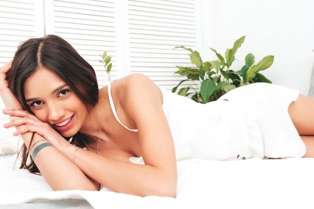 Portrait de jeune femme belle en pyjama blanc