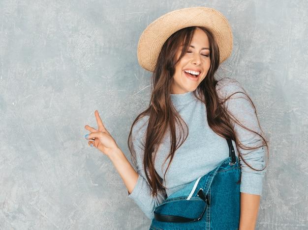Portrait de jeune femme belle à la recherche. fille à la mode dans des vêtements décontractés de salopette d'été et un chapeau ... montre le signe de la paix