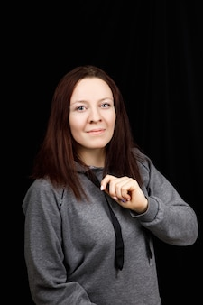 Portrait de jeune femme belle remise en forme portait un chemisier de sport gris sur fond noir.