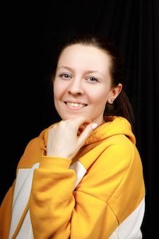 Portrait de jeune femme belle remise en forme portant un chemisier de sport jaune sur fond noir.