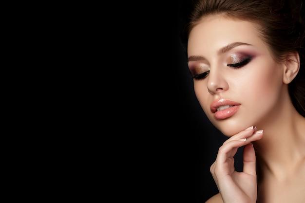 Portrait de jeune femme belle avec soirée maquillage toucher son visage sur fond noir. yeux smokey multicolores