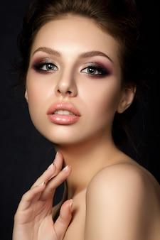 Portrait de jeune femme belle avec soirée maquillage toucher son visage sur fond noir.