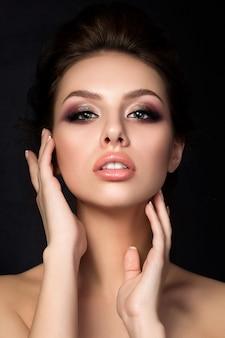 Portrait de jeune femme belle avec soirée maquillage toucher son visage sur fond noir