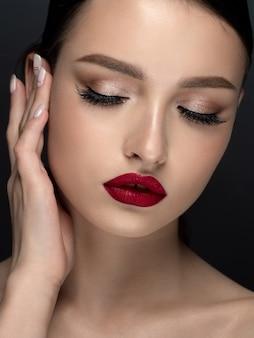 Portrait de jeune femme belle avec soirée maquillage toucher son visage. se réconcilier