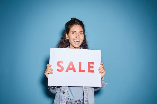 Portrait de jeune femme belle tenant une pancarte de vente et souriant sur le fond bleu