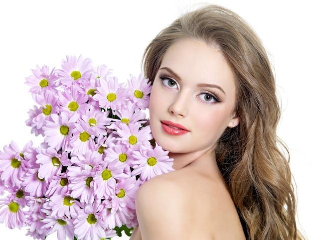 Portrait de jeune femme avec de belles fleurs de printemps sur blanc