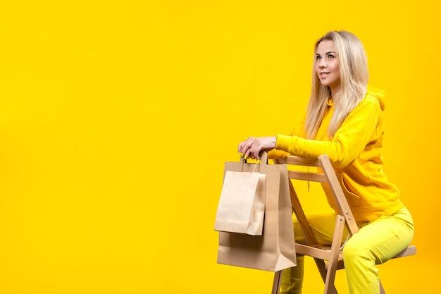 Portrait de jeune femme blonde assez caucasienne avec des sacs en papier écologique en costume sportif jaune, assis sur une chaise en bois, isolé