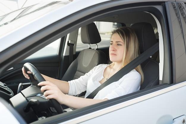Portrait de jeune femme blonde concentrée au volant d'une voiture