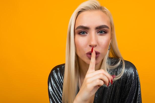 Portrait d'une jeune femme blonde demandant d'être plus calme sur un studio jaune