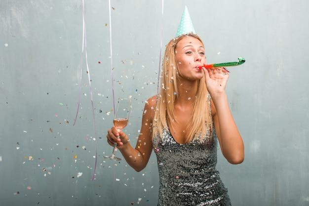 Portrait de jeune femme blonde élégante célébrant une fête.