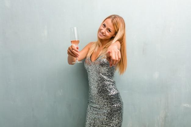 Portrait de jeune femme blonde élégante gaie. tenant un verre de champagne.