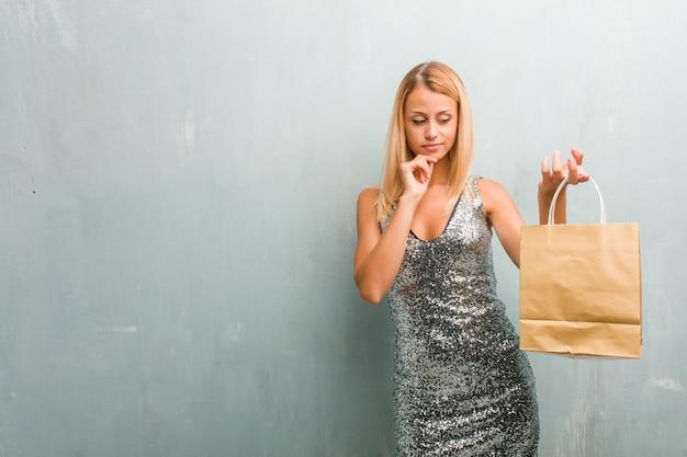 Portrait de jeune femme blonde élégante pensant et levant les yeux, confuse à propos d'une idée