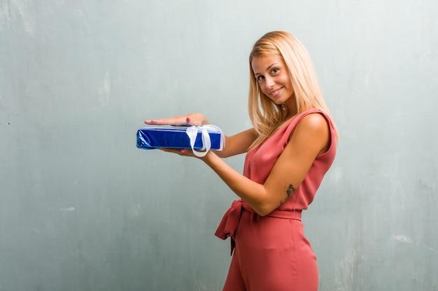 Portrait de jeune femme blonde élégante tenant quelque chose avec les mains, montrant un produit