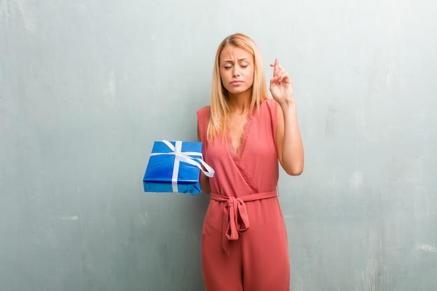 Portrait de jeune femme blonde élégante traversant ses doigts. tenant un cadeau bleu avec ruban.