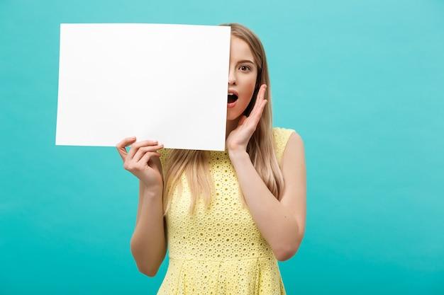 Portrait d'une jeune femme blonde étonnée tenant une pancarte blanche avec espace de copie sur fond de studio bleu. montrant un visage surprise choqué.
