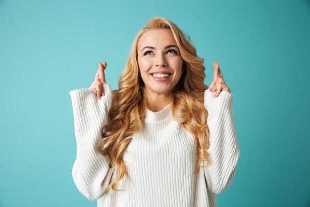 Portrait d'une jeune femme blonde excitée en pull
