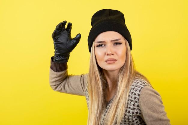 Portrait de jeune femme blonde en gants noirs et chapeau posant et debout.