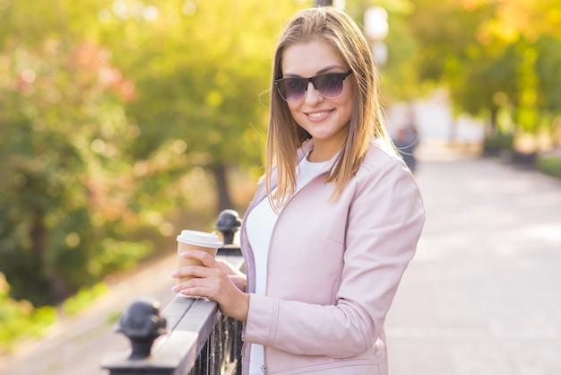 Portrait d'une jeune femme blonde heureuse et jolie avec une tasse de café dans ses mains