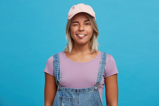 Portrait de jeune femme blonde ludique souriante porte
