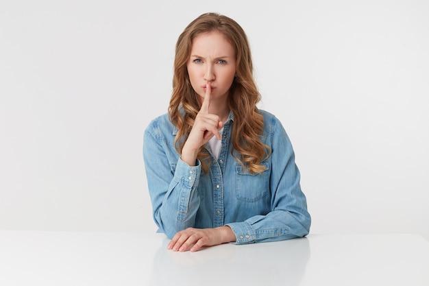 Portrait de jeune femme blonde mignonne mystérieuse porte des chemises en jean, assis à la table blanche, fronçant les sourcils et montre un geste de silence, veuillez rester calme. se dresse sur fond blanc.
