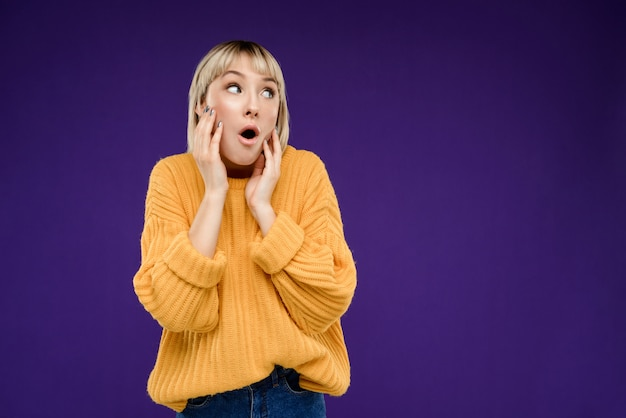 Portrait de jeune femme blonde sur mur violet espace copie