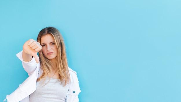 Portrait d'une jeune femme blonde nerveuse montrant le pouce vers le bas contre la toile de fond bleue