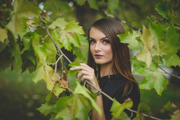 Portrait d'une jeune femme blonde posant avec des feuilles d'arbres