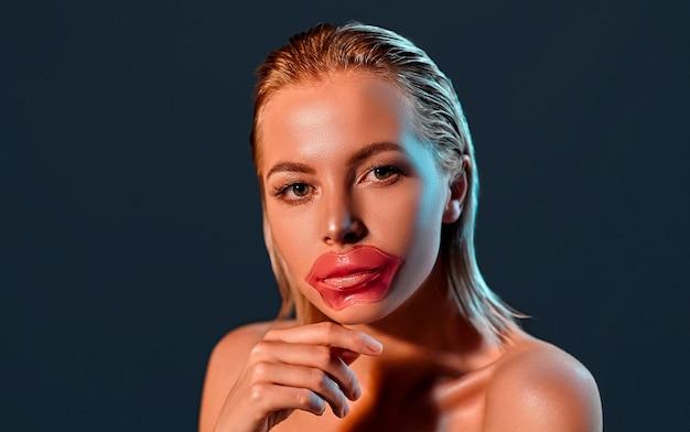 Portrait d'une jeune femme blonde séduisante avec une peau brillante avec un patch pour les lèvres sur le mur noir