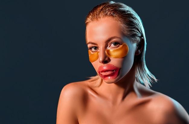 Portrait d'une jeune femme blonde séduisante avec une peau brillante avec des taches sur ses lèvres et sous ses yeux sur un mur noir