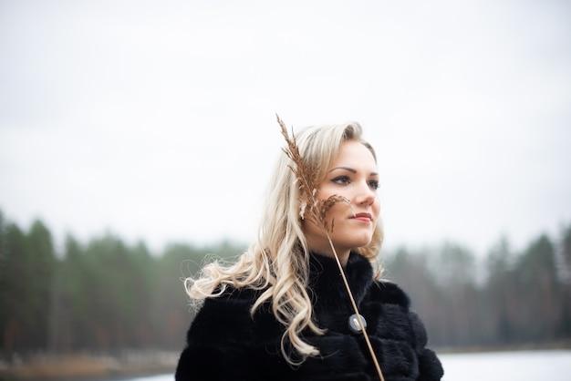 Portrait d'une jeune femme blonde sensuelle au bord du lac pendant l'hiver
