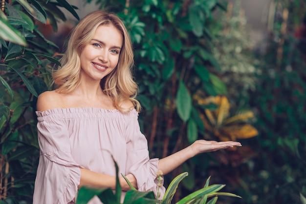 Portrait d'une jeune femme blonde souriante, debout dans le jardin présentant