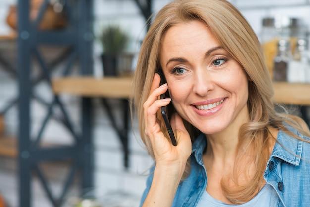 Portrait d'une jeune femme blonde souriante parlant au téléphone intelligent